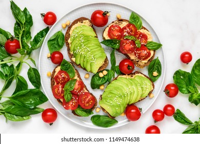Avocado and tomatoes toasts with hummus, sesame and basil in a plate over white marble background. vegan food. top view