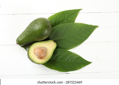 Avocado whith leafs on a board painted with white paint