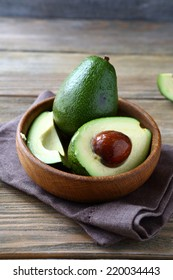 Avocado whole and halves in a wooden bowl, close up