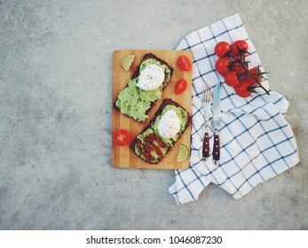 Avocado/Guacamole sandwich with poached egg, dry tomatoes on a wooden board with fresh cherry tomatoes and sliced lime. Grey concrete background. Healthy breakfast concept. Top view. Copy space