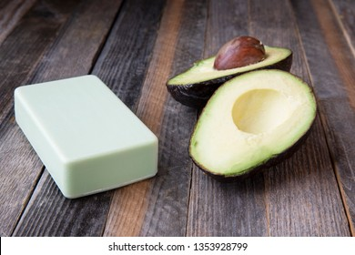 Avocados and avocado soap on wooden table.