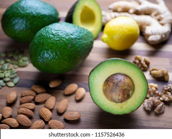 avocados and nuts on a wood cutting board.