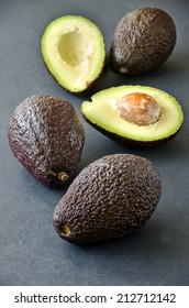 Avocados on black background, selective focus