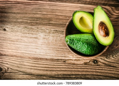 Avocados on wooden table. Avocado in  bowl. Raw fresh cut avocados.