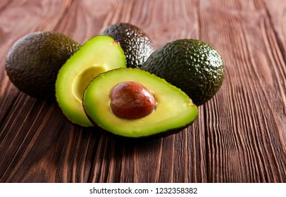 Avocados over dark wooden background, selective focus