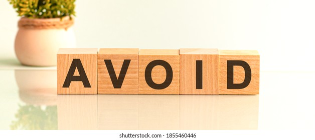 avoid word written on wood block. avoid motivation text on wooden blocks business concept white background. Front view concepts, flower in the background