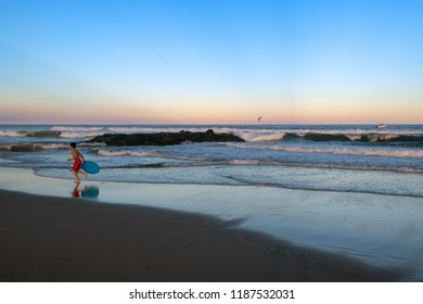 AVON BY THE SEA, NEW JERSEY-SEPTEMBER 16: A young boy with toy runs on the beach at dusk on September 16 2018 in Avon by the Sea along the Jersey shore.