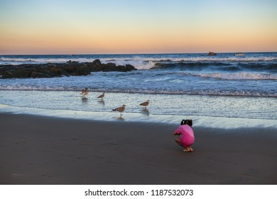 AVON BY THE SEA, NEW JERSEY-SEPTEMBER 16: A young girl looks for shells on the beach at sunset on September 16 2018 in Avon by the Sea along the Jersey shore.