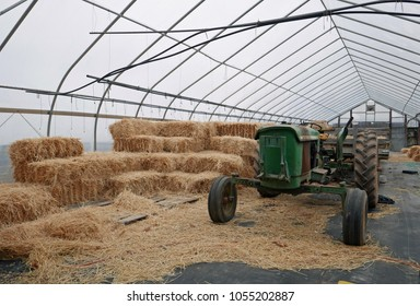 Avon, CT, USA - February 25, 2018: Old John Deere tractor with straw bales in a greenhouse