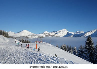 Avoriaz, France - December 19, 2017: People on the ski slopes with the resort of Avoriaz sitting above the clouds in the Portes du Soleil ski area in the French Alps.