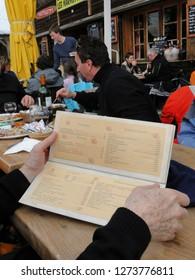 AVORIAZ, FRANCE - FEB 25, 2012 - Reading a menu at an outdoor restaurant in Avoriaz, France