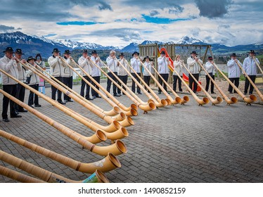 Avry-devant-Pont, Switzerland - April 27, 2019: Ensemble of Swiss alphorn (alpenhorn, alpine horn) blowers are playing outdoor for everyone. Alpin horn is a symbol of Swiss alpine traditions
