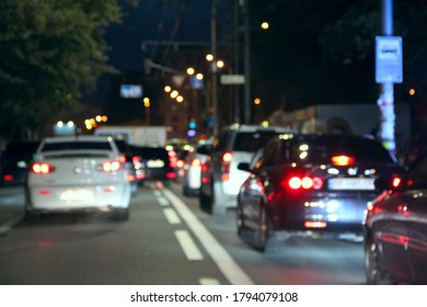 Avtomobiles with headlights and lights on in the night city. Cars with headlights on. Signal lights of transport. Line of cars on the road. Blurred picture