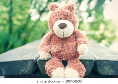 Awaiting for owner. Lonely forgotten teddy bear toy on wooden table in the park. Vintage filter. Outdoors.
