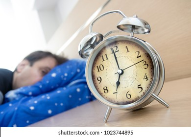 Awaked man looks at the alarm clock on table in his bedroom. Unpleasant early awakening. The alarm clock loud ringing at seven o'clock in the morning.