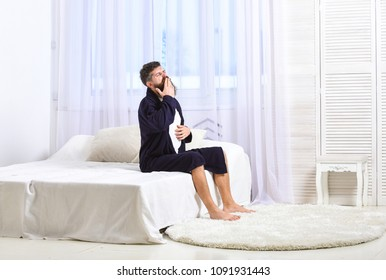 Awakening concept. Man in robe sits on bed, white curtains on background. Macho with beard and mustache sluggish getting up and yawning in morning. Guy on sleepy face yawning in morning