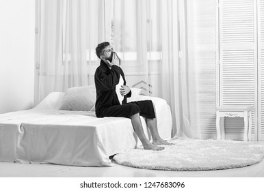 Awakening concept. Man in robe sits on bed, white curtains on background. Macho with beard and mustache sluggish getting up and yawning in morning. Guy on sleepy face yawning in morning.