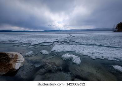 Awakening lake from ice. Frozen ice and snow by the Turgoyak lake.