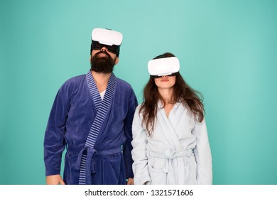 Awakening from virtual reality. Couple in bathrobes wear vr glasses. Conscious awakening. Return to reality. Man and woman explore vr. VR technology and future. VR communication. Exciting impressions.