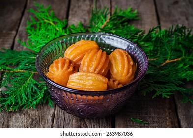 Awama(tulumba) - arabian syrup-soaked fried sponge balls honey in glass bowl on wooden background. Oriental sweets. Ramadan food