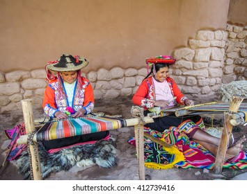 Awana Kancha, Peru MAY 26 2012: Unidentified native weavers, dressed in traditional clothing, demonstrate their handicraft.  Awana Kancha is a popular tourist attraction close to Cusco.