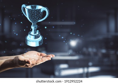 Award concept with polygonal winner trophy cup above man hand at abstract dark background.