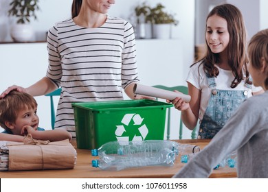Aware mother teaching smiling children how to recycle household waste