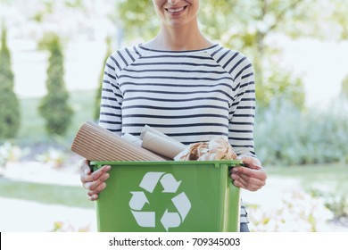 Aware woman separating paper from other waste, putting it into green container to save natural resources