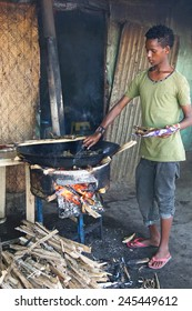 AWASSA, ETHIOPIA - NOVEMBER 16, 2014: Young Boy frying fish on the market of Awassa on November 16, 2014 in Awassa, Great Rift Valley, Ethiopia, Africa