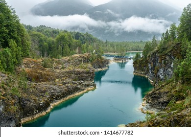 Awe hanging bridge at north Chilean Patagonia, Puelo river moves around the narrow gorge with its turquoise waters on an awe idyllic natural environment outdoor rugged landscape under a dramatic sky