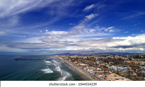 Awesome aerial birds eye view of cloudscape whispering above downtown Oceanside pier and miles of blue green and white pacific coastline on postcard picture perfect afternoon