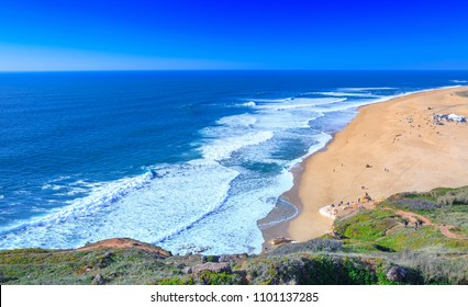 Awesome aerial sunny seascape coastline of Atlantic ocean. View North Beach (Praia do Norte). Most famous place of giant breaking waves for surfers from around the world. Nazare, Portugal.