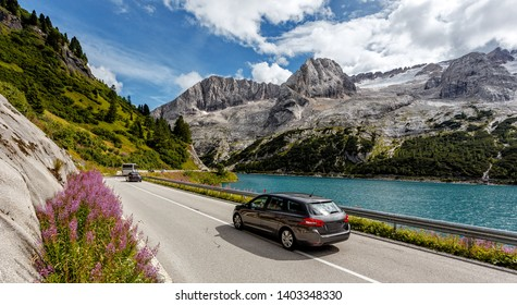 Awesome alpine highland in sunny day. Colorful spring scene. Summer view of Asphalt road near Fedaia lake and Marmolada mountain.  Amazing natural scenery in Dolomites Alps. Picture of wild area