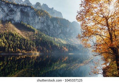 Awesome alpine highland at sunset with colorful sky. Scenic image of fairy-tale lake surrounded by Rocky Mountains in sunlit. Amazing Alps valley. Incredible autumn Landscape. Picturesque background.
