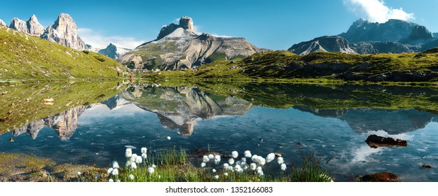 Awesome Alpine highlands in sunny day. Amazing Summer Landscape of Dolomites Alps. Wonderful Panoramic view at Mountains Range and calm lake on foreground of Tre Cime di Lavaredo National park