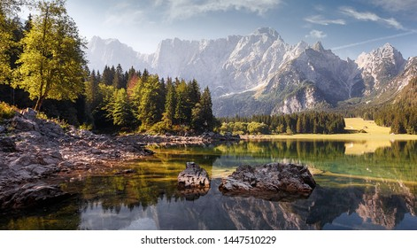Awesome alpine highlands in sunny day. Scenic image of fairy-tale lake during sunset.  Majestic Rocky Mountains on background. Wild area. Fusine lake. Italy, Julian Alps. Best travel locations.