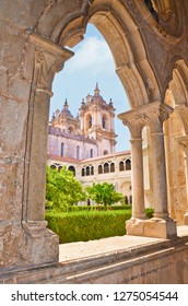 Awesome arch window view of the main church in the Alcobaca Monastery complex in Portugal. The Gothic cathedral is surrounded by inner courtyard. The building is part of UNESCO World Heritage.