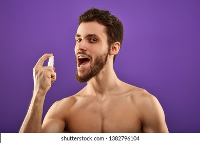awesome attractive man applying fresh breath spray. close up portrait.man spraying medicine in the mouth.man preparing for a date