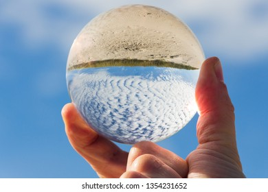 awesome beach with interesting clouded sky shown through a hand-held crystal ball