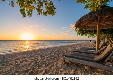 awesome beach at Mauritius island with wooden parasol in the right side, amazing sunset.