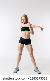 awesome beautiful sportswoman stretching arms and looking away. full length photo. fitness, health, body care