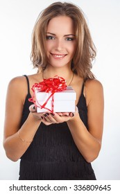 Awesome brunette woman in black dress holds gift box. Isolated on white background.