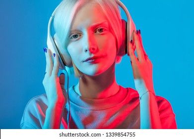 awesome Caucasian albino girl concentrated on music, close up photo. education, girl learning the language by the headphones, method of studing