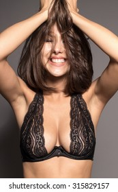 Awesome Caucasian attractive joyful happy sexy female model is shaking head with brunette hair in studio wearing black transparent lingerie, isolated on gray background