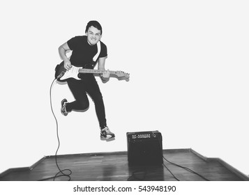 Awesome crazy fashion young rock guitar player jumps with passion in studio. Black and white toned. White background.