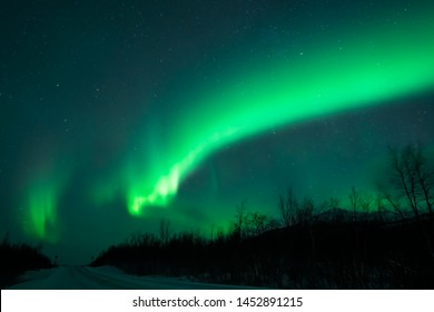 Awesome display of aurora borealis northern lights above empty snow covered road in Norway and Finland