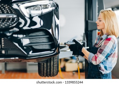 awesome fair-haired woman changing car wheel in auto repair shop. close up side view shot. job, profession