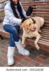Awesome female with long black hair in winter clothes possing with a dog.
