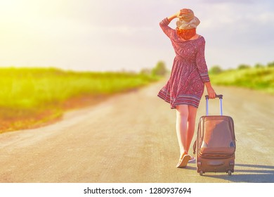 Awesome female in summer dress and hat hitchhiking with suitcase. Woman walking on the road with baggage at sunny day. Travel concept