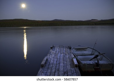 An awesome fishing lake is displayed with a bright moon reflecting off the water.